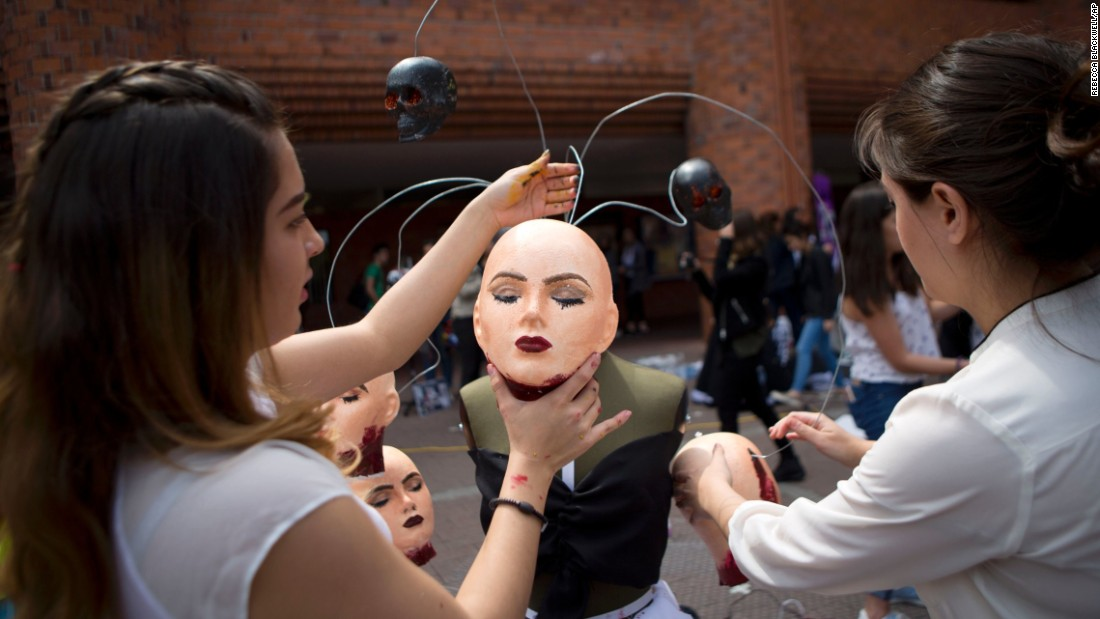 Fashion students in Mexico City hang styrofoam heads atop a dressmaker's dummy during a competition on Wednesday, March 16. The fashions were supposed to be inspired by the effects of the drug trade on Mexican culture.
