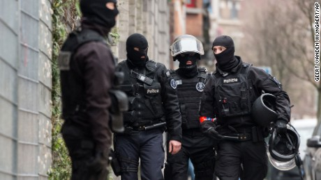Police officers stand guard during a raid in the Molenbeek neighborhood of Brussels, Belgium, Friday March 18, 2016. Police have descended in force to search a residence in the Molenbeek, and Belgian media reported gunshots had been fired. RTBF French-language TV reported late Friday afternoon that two people had been wounded, and that one might be Paris attacks fugitive Salah Abdeslam. (AP Photo/Geert Vanden Wijngaert)