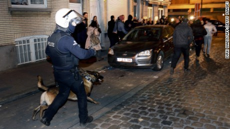A policeman and a police dog face a crowd  during a police operation in the Molenbeek-Saint-Jean district in Brussels, on March 18, 2016, as part of the investigation into the Paris November attacks.