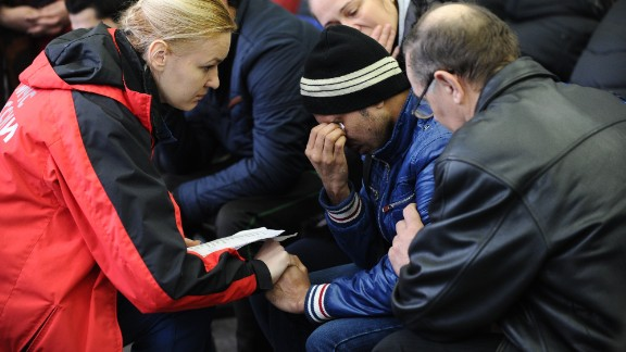 A Russian Emergency Situations Ministry employee (L) tries to comfort a relative of the plane crash victims at the Rostov-on-Don airport.