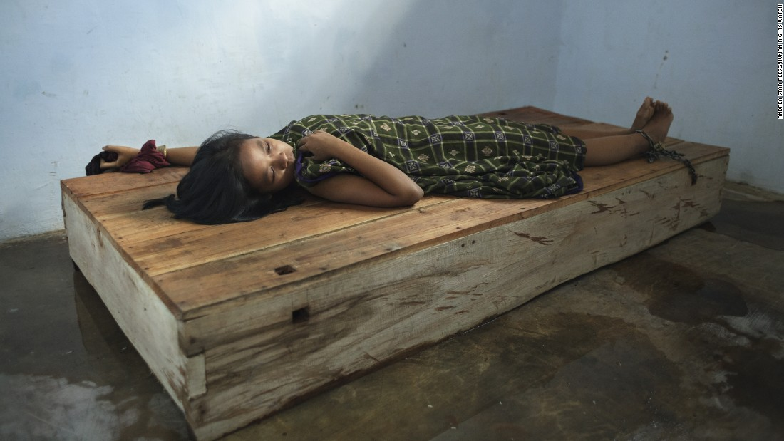"A 24-year-old female resident lies with her wrist and ankle chained to a platform bed at Bina Lestari healing center in Brebes, Central Java. After her husband abandoned her and her 5 year-old daughter, she began to suffer from depression, <a href=""https://www.hrw.org/node/287537/"" target=""_blank"">HRW said in the report.</a>"
