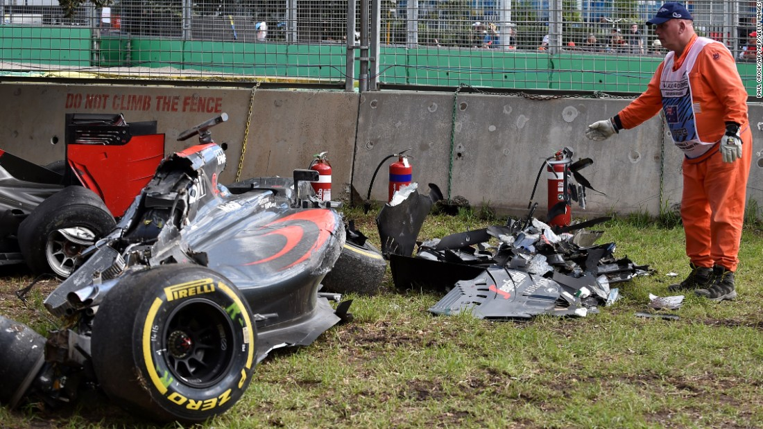 "A track marshall examines debris following the crash. Alonso recalled: ""You are just flying and then you see the sky, the ground, the sky, the ground."""