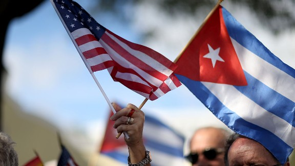 MIAMI, FL - DECEMBER 20: A protester holds an American flag and a Cuban one as she joins with others opposed to U.S. President Barack Obama