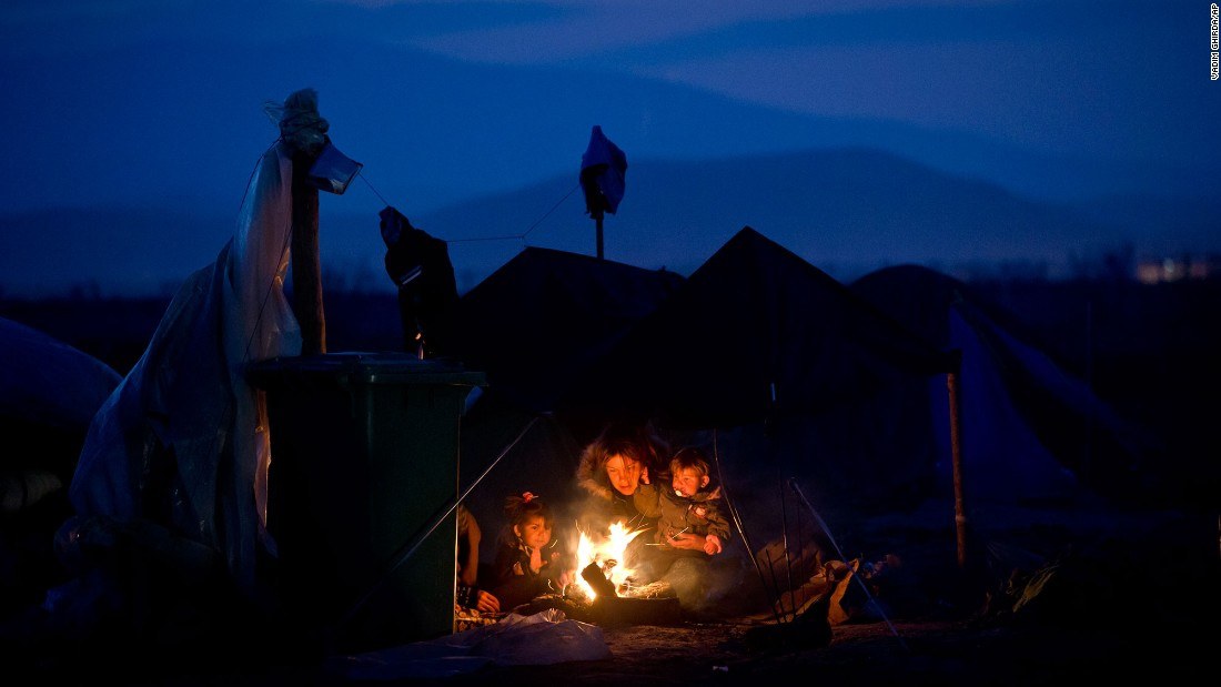 A woman sits with children around a fire at the northern Greek border point of Idomeni in March 2016.