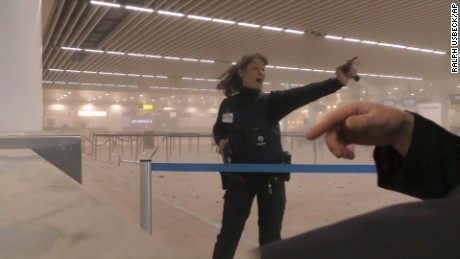 In this photo provided by Ralph Usbeck a police officers directs passengers in a smoke filled terminal at Brussels Airport, in Brussels after explosions Tuesday, March 22, 2016. Authorities locked down the Belgian capital on Tuesday after explosions rocked the Brussels airport and subway system, killing  a number of people and injuring many more. Belgium raised its terror alert to its highest level, diverting arriving planes and trains and ordering people to stay where they were. Airports across Europe tightened security.  (Ralph Usbeck via AP)