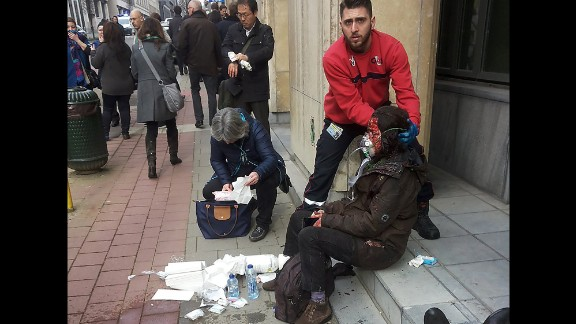A private security guard helps a wounded woman outside the Maelbeek metro station.