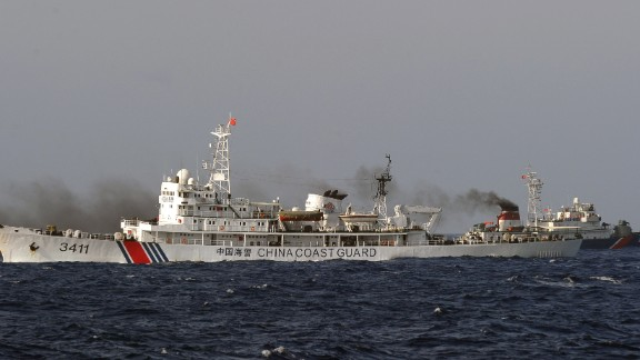 This picture taken from a Vietnam Coast Guard ship on May 14, 2014 shows a Vietnamese Coast Guard ship (R, dark blue) speeding up away from a  China Coast Guard ship  near to the site of a Chinese drilling oil rig (R, background) being installed at the disputed water in the South China Sea off Vietnam