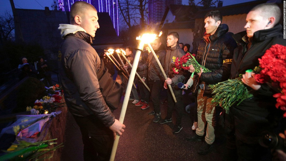 Servicemen with Azov, a Ukrainian volunteer battalion, hold torches during a tribute ceremony at the Belgian Embassy in Kiev, Ukraine, on March 22.