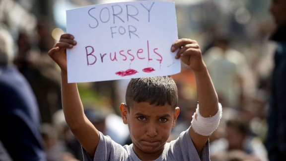 A boy at a makeshift migrant camp shows support for the victims near the village of Idomeni, Greece, on March 22.