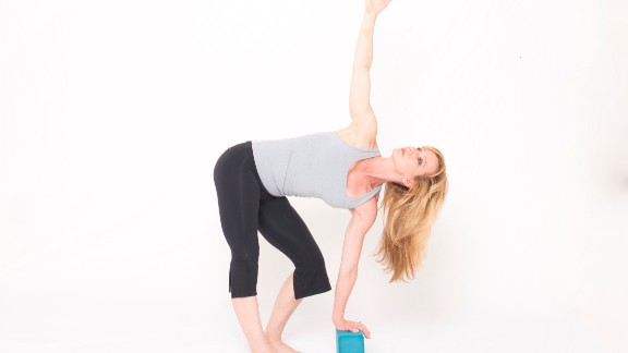 From standing, use an exhalation to squat down and place your left hand on top of a yoga block or other similar support. Inhale as you reach your right arm forward and up, rotating from your shoulder, midback and rib cage to twist open to the right. At the same time, straighten your right leg while pulling back through your heel as if you're sliding it backward. You should experience a stretch in the back of your leg and across your right low back. Hold for five breaths, using respiration to facilitate the twist. Focus inhalations on the open side of your rib cage (the side you're turning toward) and exhalations on the opposite side, employing side waist muscles to internally rotate your ribs for greater rotation. Unwind back to standing and repeat the movement with rotation to the left.