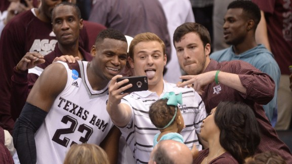 """After his team pulled off <a href=""""http://bleacherreport.com/articles/2626376-texas-am-goes-on-14-2-run-in-31-seconds-to-send-game-to-ot-vs-northern-iowa"""" target=""""_blank"""" target=""""_blank"""">one of the greatest comebacks in college basketball history,</a> Texas A&M guard Danuel House celebrates with fans in Oklahoma City on Sunday, March 20. The Aggies trailed Northern Iowa by 12 points with less than a minute to play in regulation, but they rallied to win in double overtime."""