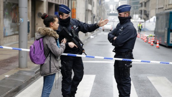 Belgian police officers standing guard near Maelbeek - Maalbeek subway station speak with a bypasser in Brussels on March 23, 2016, a day after triple bomb attacks in the Belgian capital killed about 35 people and left more than 200 people wounded. A series of explosions claimed by the Islamic State group ripped through Brussels airport and a metro train on March 22, killing around 35 people in the latest attacks to bring bloody carnage to the heart of Europe.  AFP PHOTO / KENZO TRIBOUILLARD / AFP / KENZO TRIBOUILLARD        (Photo credit should read KENZO TRIBOUILLARD/AFP/Getty Images)