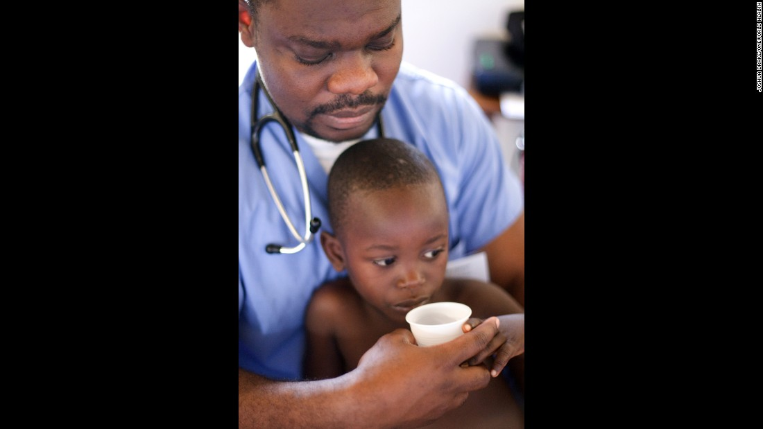OneWorld Health volunteer Dr. Kojo Abbeqquaye assists a young child in Uganda.