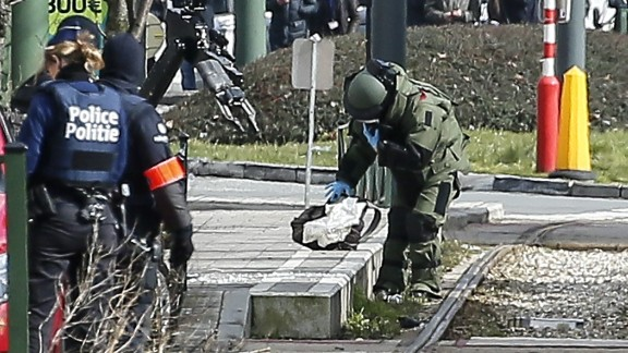 epa05230635 A Belgian bomb disposal expert in heavy protection gear (C) examines a suspicious object at the scene of an apparent operation against terror suspects near the Meizer round about in the Schaerbeek district of Brussels, Belgium, 25 March 2016. Media reported the sound of gunfire and explosions during the raid which is believed to be linked to the investigation into the 22 March Brussels terrorist attacks which caused the death of at least 31 people and injured hundreds of others and for which the so-call 'Islamic State' (IS) had claimed responsibility. According to Belgian RTBF broadcasting company one person was arrested in the operation.  EPA/JULIEN WARNAN