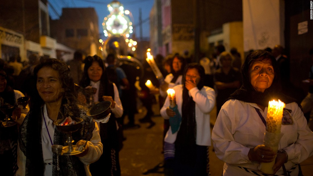 The faithful light candles during a Good Friday procession in Lima, Peru.