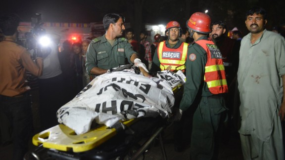 Rescuers use a stretcher to shift a body from the bomb blast site.