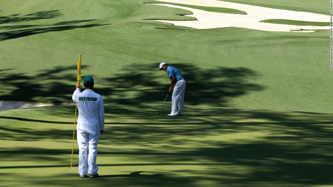 Foster tends the flag while Westwood putts  on the 10th green during the second round of the 2010 Masters. Westwood led going into the final round that year but eventually had to settle for second place behind winner Phil Mickelson.