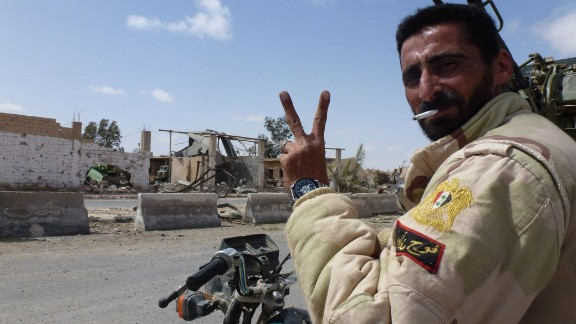 A member of the Syrian pro-government forces flashes the V-sign in a residential neighborhood of the modern town of Palmyra.