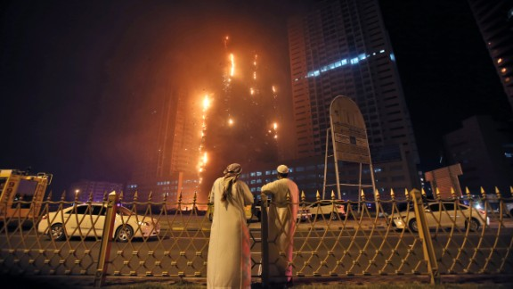 Two Emirati officials watch a fire spread up the side of a high-rise building in Ajman, United Arab Emirates, on Tuesday.