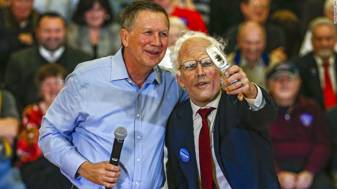 Ohio Gov. John Kasich, a Republican presidential candidate, poses with a man impersonating U.S. Sen. Bernie Sanders during a campaign event in Palatine, Illinois, on Wednesday, March 9.