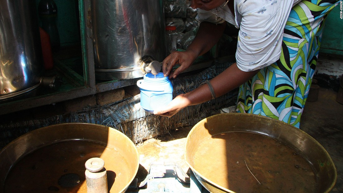 A tub of honey is filled at a local Bonga shop. Tubs of honey of varying shades of color are on sale, from dark caramel to light amber to opaque white.