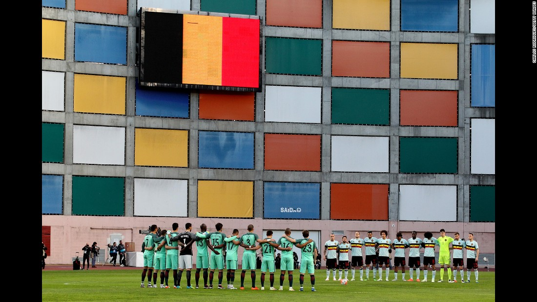 "The Belgian national football team, right, and the Portuguese national team observe a minute of silence Tuesday, March 29, for the victims of the <a href=""http://www.cnn.com/2016/03/22/world/gallery/belgium-airport-explosion/index.html"" target=""_blank"">Brussels terror attacks.</a> The international friendly match, initially scheduled for the Belgian capital, was moved to Leiria, Portugal."