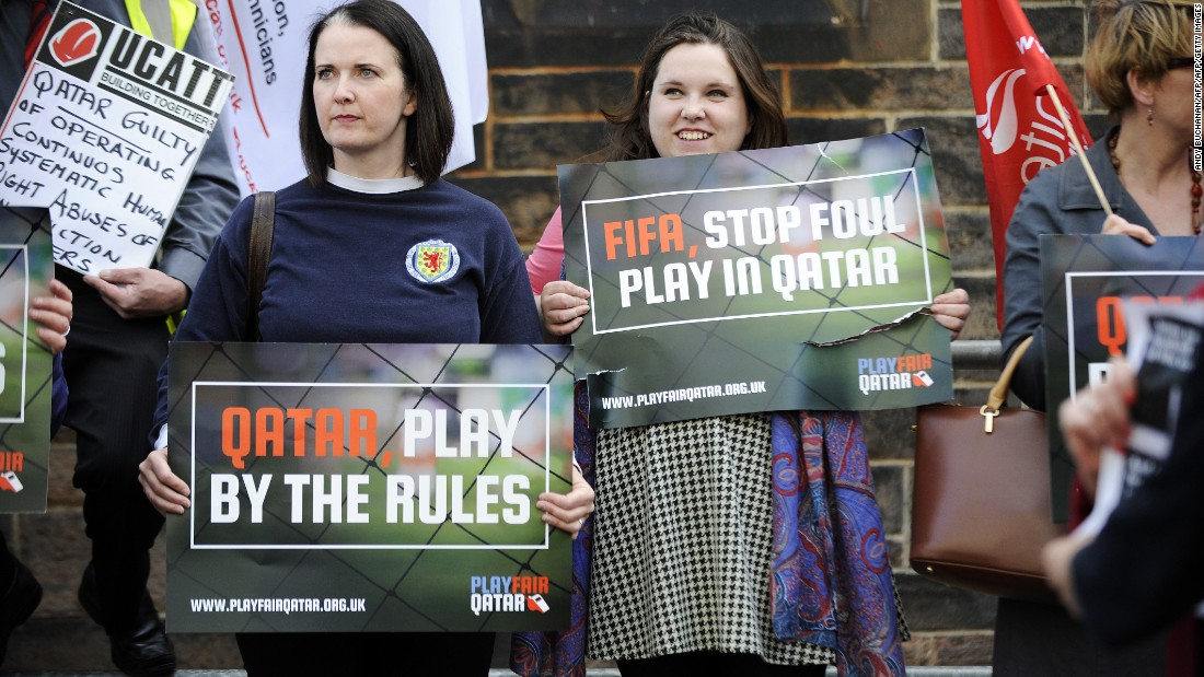 Demonstrators hold placards calling for change to Qatar's policies on the working conditions of migrant workers ahead of the international friendly between Scotland and Qatar in Edinburgh in June 5, 2015.