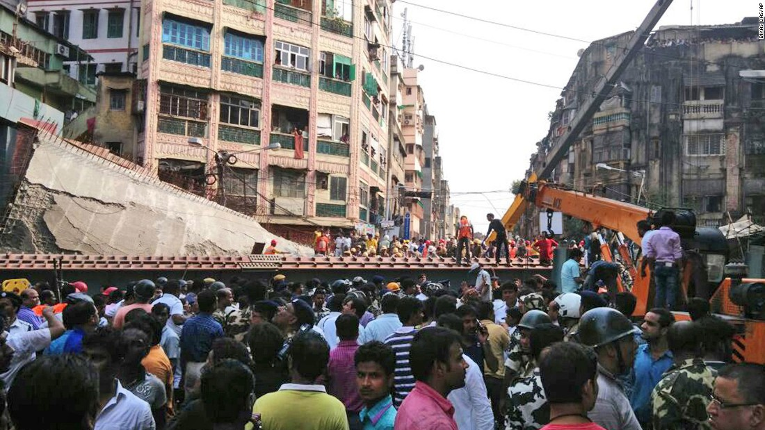 People watch as residents and rescue workers clear the debris on March 31.