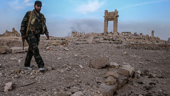 After: A Syrian government soldier walks near what