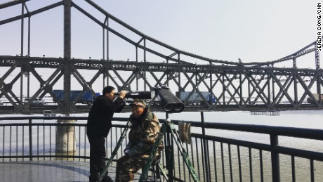 A Chinese tourist peeks into North Korea through a pair of binoculars at the border in Dandong, China. A look costs 5 yuan or 80 U.S. cents.