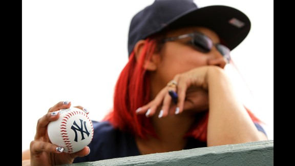 A New York Yankees fan holds an autograph ball over the dugout wall during a spring-training game in Jupiter, Florida, on March 8.