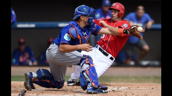 Washington's Scott Sizemore slides safely into home, beating a tag by New York Mets catcher Travis d'Arnaud during a game in Viera, Florida, on March 11.