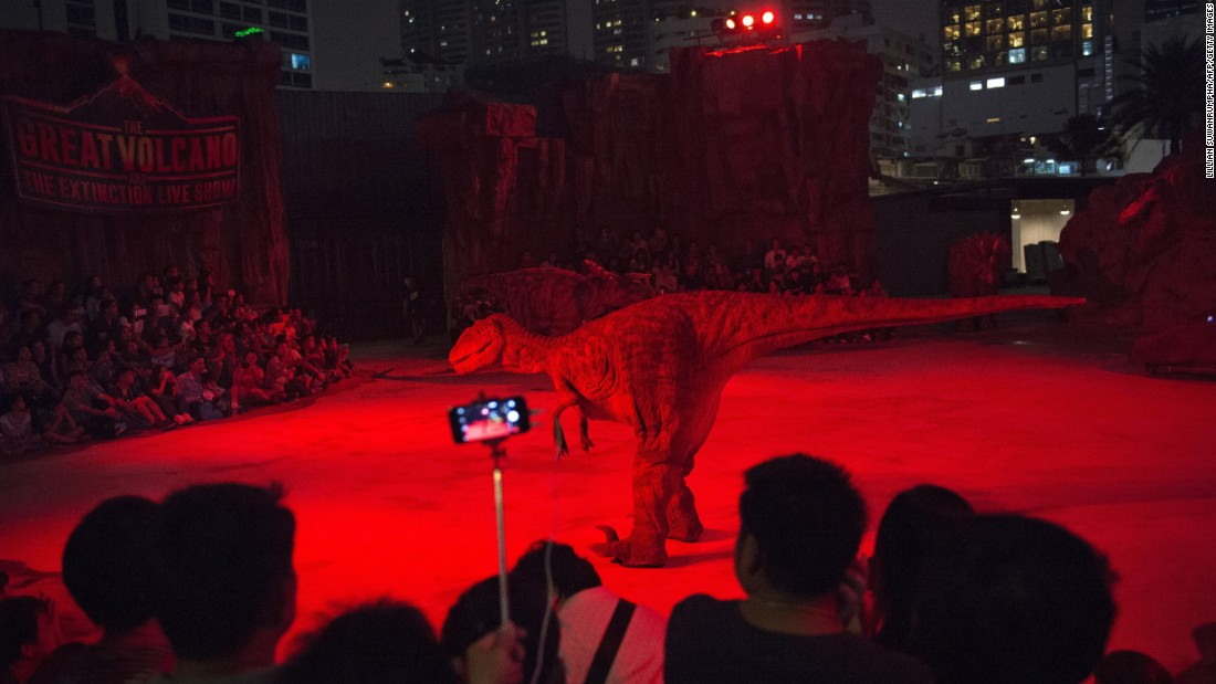 People watch a show at Dinosaur Planet, a new theme park in Bangkok, Thailand, on Monday, March 28.