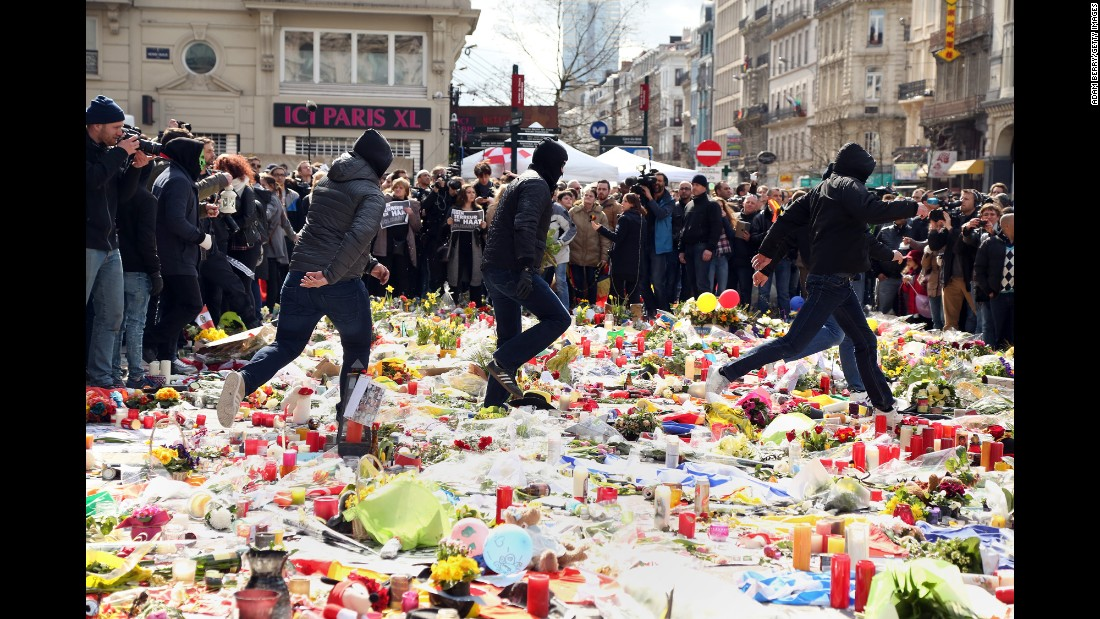 "Right-wing protesters trample over flowers and candles in Brussels, Belgium, as they interrupt a vigil held Sunday, March 27, for victims of <a href=""http://www.cnn.com/2016/03/22/world/gallery/belgium-airport-explosion/index.html"" target=""_blank"">the recent terror attacks.</a> The protesters raised their arms in Nazi salutes and shouted anti-immigrant slogans. Mourners countered the chants with their own: ""No to hatred"" and ""We are all the sons of immigrants."""