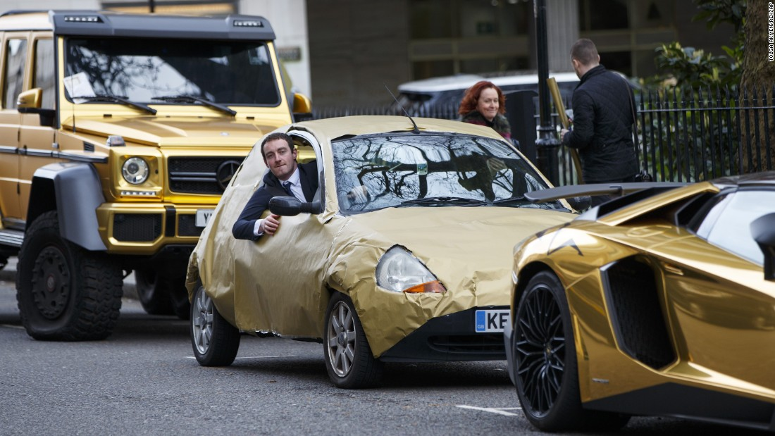 "A reporter parks his car, covered in gold wrapping paper, next to <a href=""http://www.cnn.com/2016/03/30/europe/gold-cars-saudi-london/"" target=""_blank"">a fleet of gold-painted luxury cars</a> in London on Wednesday, March 30. The luxury cars, valued at more than $1.8 million, were thought to belong to a young Saudi man who was visiting the city."