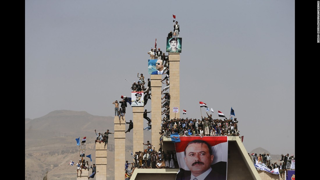 Supporters of former Yemeni President Ali Abdullah Saleh climb pillars of the Unknown Soldier Monument during a rally in Sanaa, Yemen, on Saturday, March 26. The rally marked the one-year anniversary of Saudi-led airstrikes in the country.