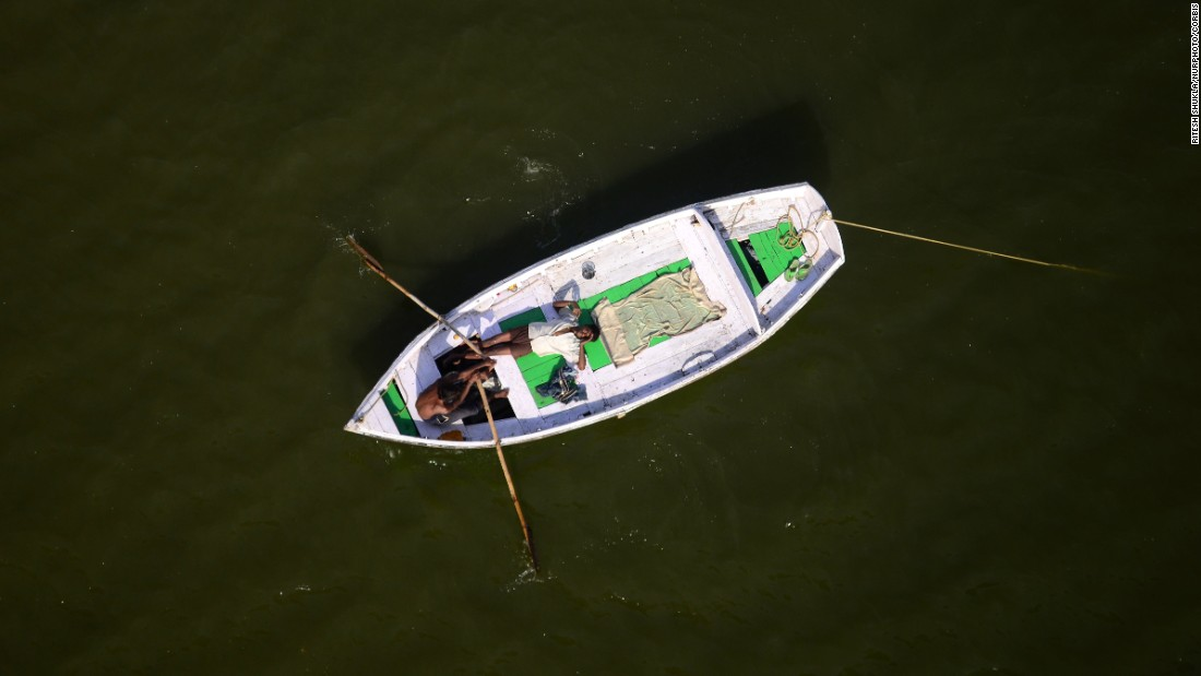 A man rows a boat as another man rests in Allahabad, India, on Tuesday, March 29.