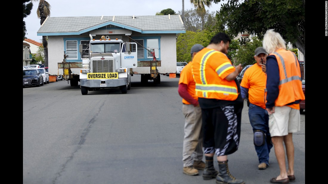 Workers in San Diego plan their next move as they transport a house on Monday, March 28.