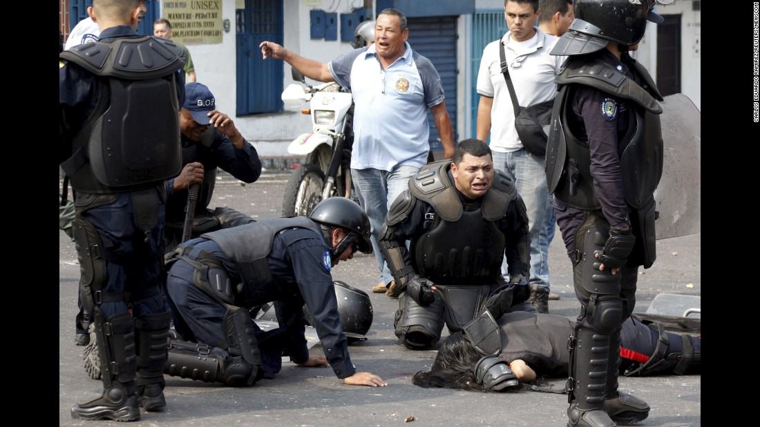 "Police officers in San Cristobal, Venezuela, react after their colleague was run over by a bus during a protest on Tuesday, March 29. <a href=""http://www.businessinsider.com/r-two-venezuelan-police-officers-killed-in-protest-2016-3"" target=""_blank"">Two police officers were killed</a> when they were hit by a bus driven by men protesting an increase in the price of public transportation."