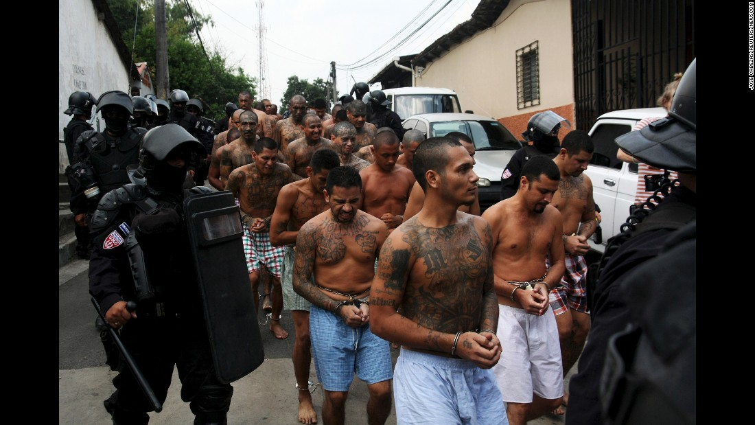 Gang members are guarded by police as they arrive at a jail in Quezaltepeque, El Salvador, on Tuesday, March 29.