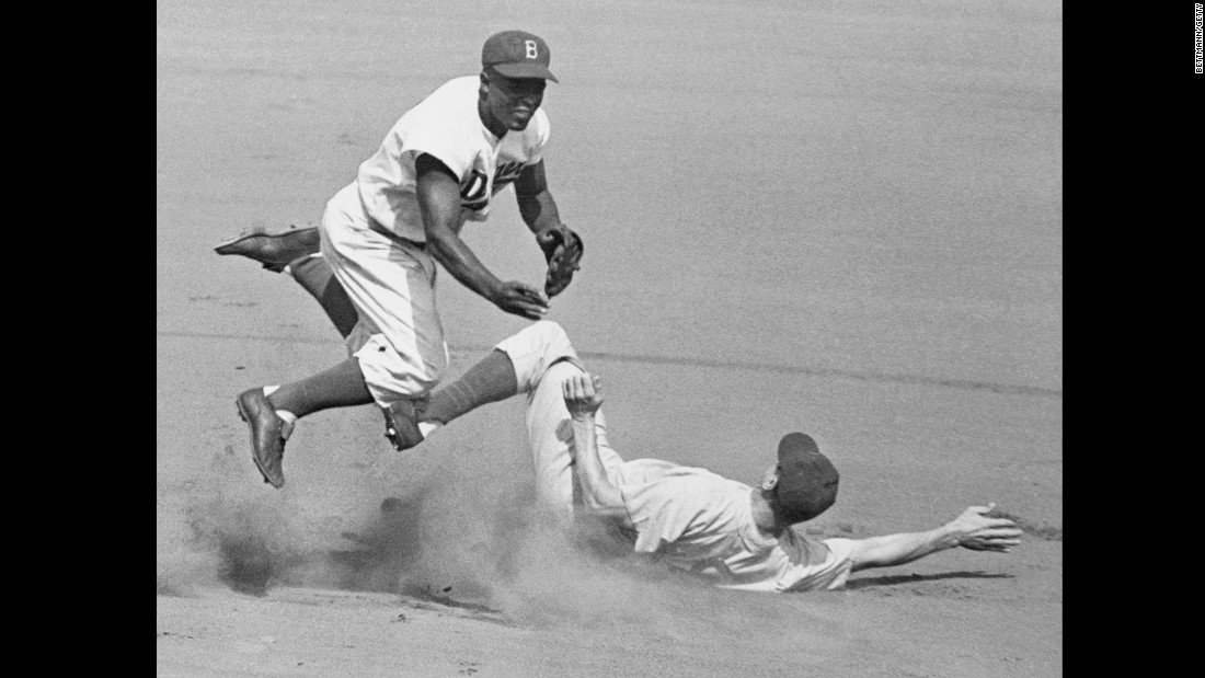Robinson played several positions for the Dodgers: mainly second base but also third base, first base and a little outfield. Here he leaps into the air in an attempt to make a double play as the Cubs' Hank Sauer slides into second in a 1952 game.