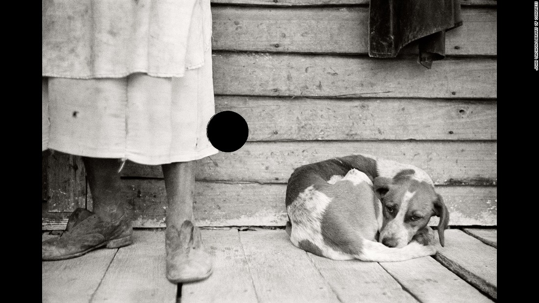 "A sharecropper and dog are photographed in North Carolina in 1938. ""It is certain that Stryker's use of a hole punch was strictly utilitarian; his only goal was to destroy negatives,"" McDowell wrote. ""But in his act of censoring what images were 'suitable' for printing, Stryker unwittingly created a new picture, one that belonged neither to the mission of the photographer (nor to that of) the FSA."""