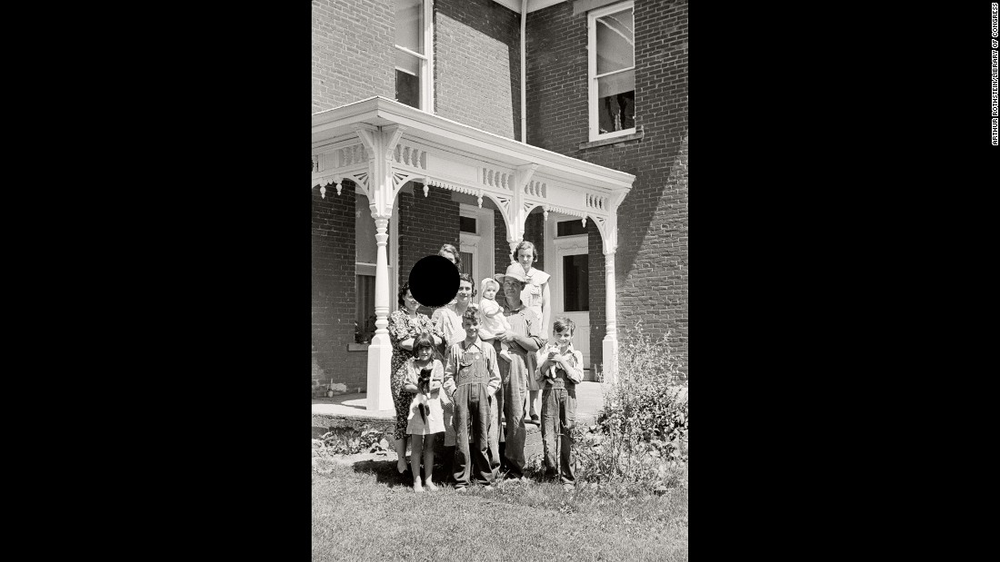 "A family poses for a photo at an Ohio farm in 1938. ""When I first began working with the killed negatives, I was disturbed by the images of people whose faces had been excised by the hole punch,"" McDowell says in the book. ""In fact, early on that motivated me to digitally repair the hole and show the restored version along with the hole-punched one. But I kept coming back to the feeling that the black-holed images were far more fascinating ... and that the violation (or violence) embedded in them had the potential to signify so much."""