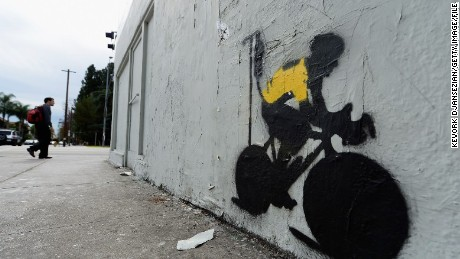 A stencil graffiti depicting Armstrong in a Tour leader's yellow jersey, attached to an IV drip.