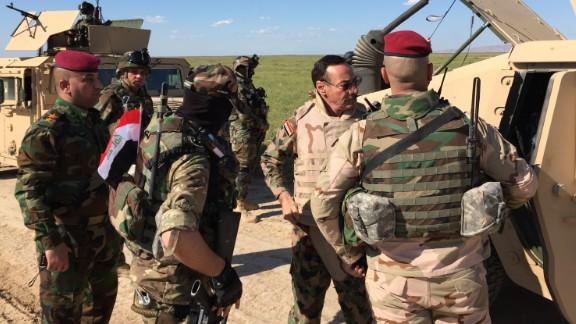 Major General Najim al-Jobori (wearing sun glasses) puts on body armor as his team heads for the front line.