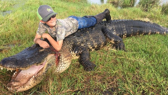 Mason Lightsey on top of the alligator that was hunted at Outwest Farms in Florida.