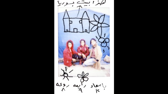 """There are drawings on this Polaroid of Asmaa, 12; Rabea, 9; and Raoah, 8. """"This is our house in Syria,"""" it says on top."""