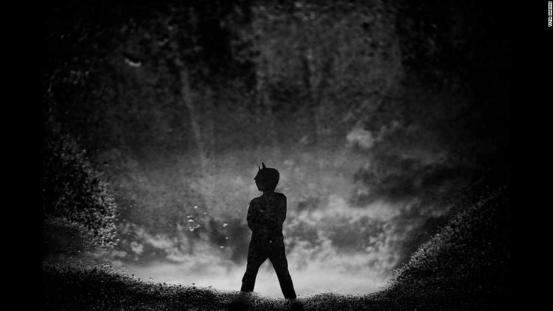 """We had a big storm blow through before bed,"" Habing said of this photo. ""After it passed, (Tharin) ran outside in his PJs with his Batman mask. He stood right in front of a massive puddle and struck the Batman pose."""
