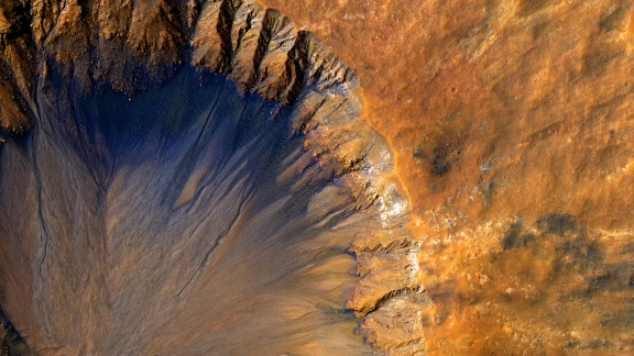 """This impact crater appears relatively recent as it has a sharp rim and well-preserved ejecta.  The steep inner slopes are carved by gullies and include possible recurring slope lineae on the equator-facing slopes. Fresh craters often have steep, active slopes, so we are monitoring this crater for changes over time.  The bedrock lithology is also diverse. The crater is a little more than 1-kilometer wide.  Note: When we say """"fresh,"""" we mean on a geological scale. The crater is quite old on a human scale.  The University of Arizona, Tucson, operates HiRISE, which was built by Ball Aerospace & Technologies Corp., Boulder, Colorado. NASA's Jet Propulsion Laboratory, a division of the California Institute of Technology in Pasadena, manages the Mars Reconnaissance Orbiter Project and Mars Science Laboratory Project for NASA's Science Mission Directorate, Washington.  NASA/JPL-Caltech/Univ. of Arizona"""