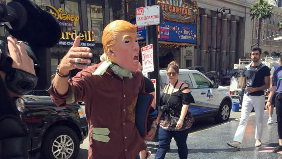 """A Trump look-alike seeks cash tips in exchange for posing with tourists because """"this Donald is broke."""""""